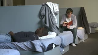 Men Lying On Beds In Homeless Shelter