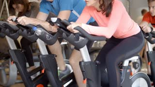Mid section of a group on exercise bikes spinning at a gym