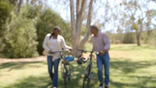 Middle aged Black couple walking with bicycles in a park