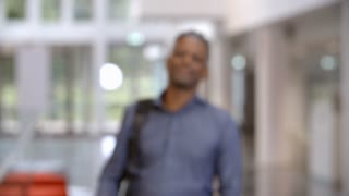Middle aged black male teacher walking into focus in a lobby