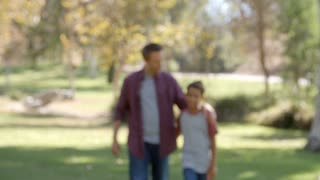 Mixed race Asian boy and father walk in to focus in park