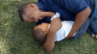 Mixed race black father play fighting with young son in park