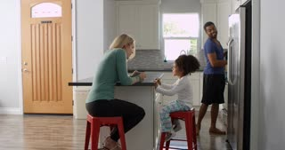Mixed race couple and daughter talk in kitchen, full length, shot on R3D