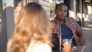 Mixed race couple talking at a table outside a coffee shop