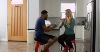 Mixed race couple talking over breakfast in the kitchen, shot on R3D