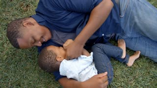 Mixed race dad lies tickling young son on the grass in park