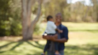 Mixed race father carrying son outdoors walks into focus