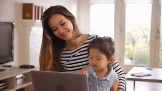 Mother And Daughter Watch Movie On Laptop At Home Together