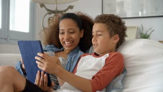 Mother And Son On Sofa Using Digital Tablet