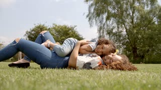 Mother and young daughter lying on grass, low angle close up