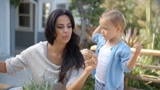 Mother At Home With Daughter Eating Meal In Garden