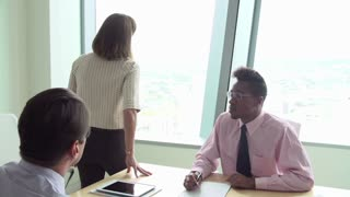 Motivational Speaker Talking To Businesspeople In Boardroom