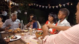 Multi generation black family eating food at table outdoors