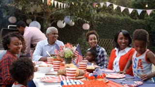 Multi generation black family talking at 4th July barbecue