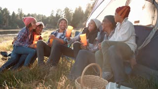 Multi generation family on camping trip sit outside tent