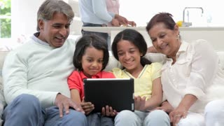 Multi-Generation Indian Family With Digital Tablet