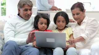 Multi-Generation Indian Family With Laptop Sitting On Sofa