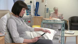 Nurse Checking On Female Patient Having Chemotherapy