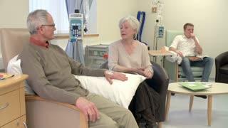 Nurse Checking On Senior Male Patient Having Chemotherapy
