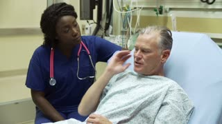 Nurse Examining Mature Male Patient In Hospital Bed