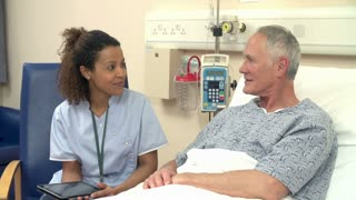 Nurse Sitting By Male Patient's Bed Using Digital Tablet
