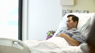 Nurse Talks To Male Patient In Hospital Room