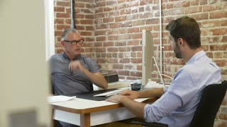 Older Businessman Interviewing Male Job Applicant In Office