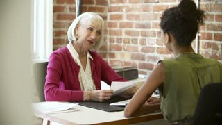Older Businesswoman Interviewing Younger Woman In Office