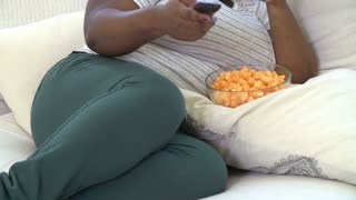 Overweight Woman At Home Eating Snacks And Watching TV