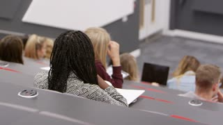 Pan across students to teacher presenting in lecture theatre, shot on R3D