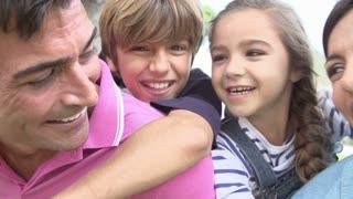 Parents Giving Children Piggyback Ride In Garden
