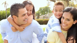 Parents Giving Children Piggyback Ride In Park
