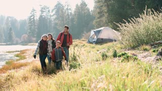 Parents on a camping trip with two kids walking near a lake