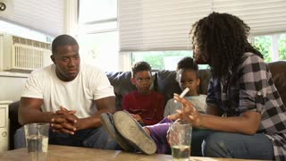 Parents Sit On Sofa With Children Having Argument
