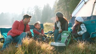Parents with two kids on a camping trip sitting outside tent