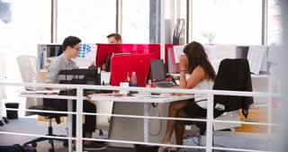 People Working At Desks In Modern Open Plan Office