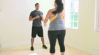 Personal Trainer Exercising With Overweight Woman