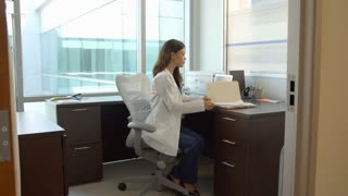 Portrait Of Female Doctor Working At Desk In Office