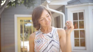 Portrait Of Happy Woman Standing Outside New Home With Keys