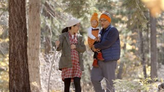 Pregnant Asian mother, husband and daughter hiking in forest