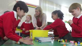 Pupils And Teacher Tidying Up Coloured Blocks