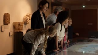 Pupils On School Trip To Museum Looking At Map Shot On R3D