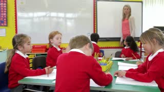 Pupils Sitting Around Table As Teacher Stands By Whiteboard