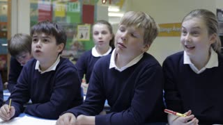 Pupils Sitting At Desks Answering Questions From Teacher