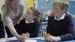 Pupils Working At Table With Teacher Helping Them