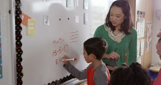Pupils writing on board with teacher in school maths class
