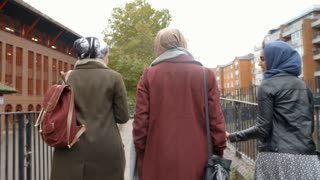 Rear View Of British Muslim Female Friends Walking In City