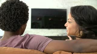 Rear View Of Couple Sitting On Sofa Watching Television