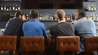 Rear View Of Male Friends Watching Game In Sports Bar