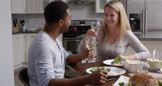 Romantic mixed race couple making a toast at meal in kitchen, shot on R3D